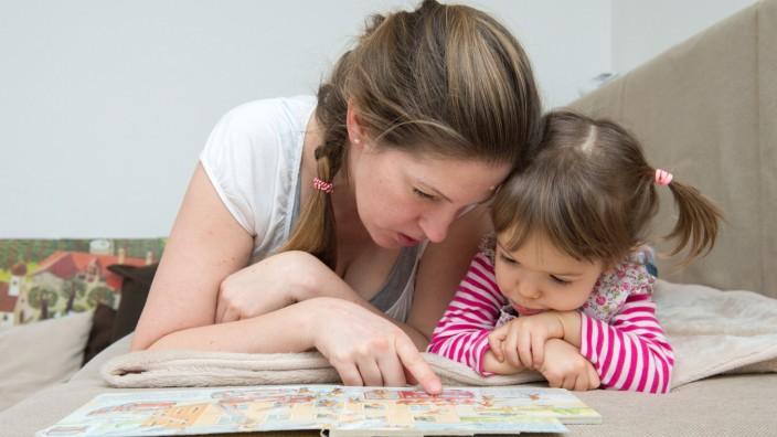 Mutter und Kind sehen sich gemeinsam ein Bilderbuch an