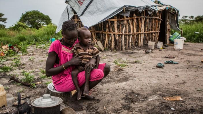 Welternährungsprogramm: Südsudan: Eine Frau bereitet Mais zu, das ein Flugzeug im Auftrag der Welternährungsorganisation in der Krisenregion abgeworfen hat.
