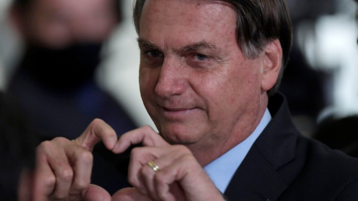 Brazil's President Jair Bolsonaro gestures after attending the launching ceremony of the New Credit of the Housing by settlers at the Planalto Palace in Brasilia