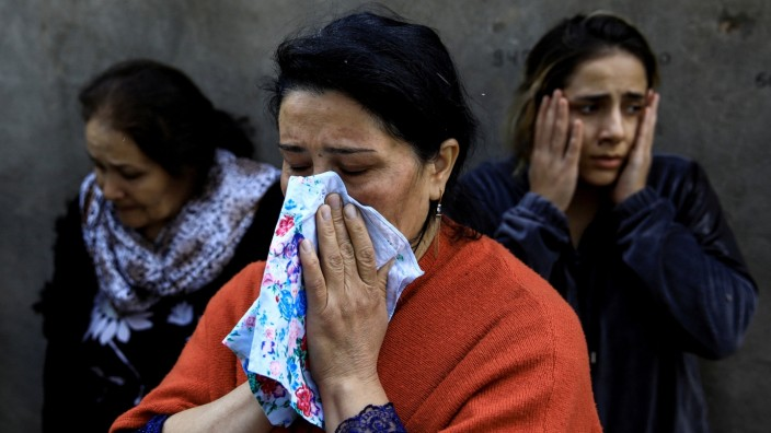 Women cry as their relatives are missing under the debris of a blast site hit by a rocket during the fighting over the breakaway region of Nagorno-Karabakh in the city of Ganja
