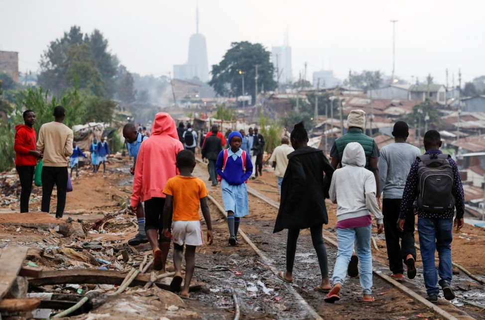 A schoolgirl walks among residents along the Kenya-Uganda railway line during the partial reopening of schools, in Nairobi