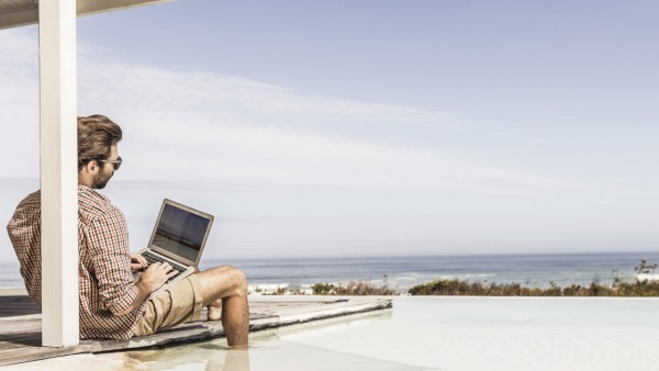 Man working on laptop next to pool at a beach house model released Symbolfoto property released PUBLICATIONxINxGERxSUIxA