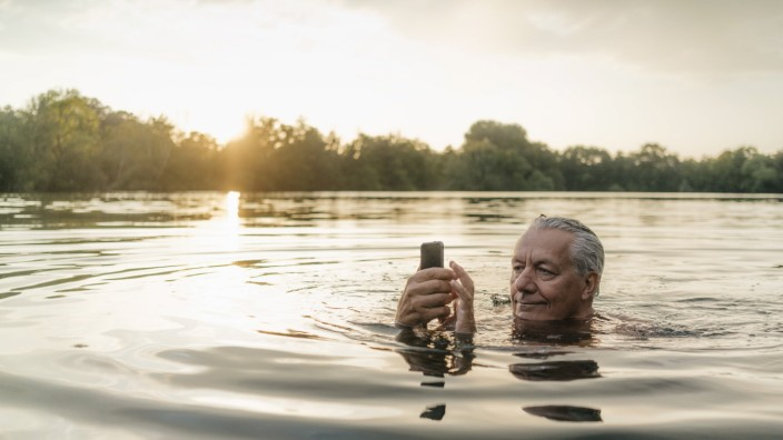 Senior man swimming in a lake at sunset using cell phone model released Symbolfoto PUBLICATIONxINxGE