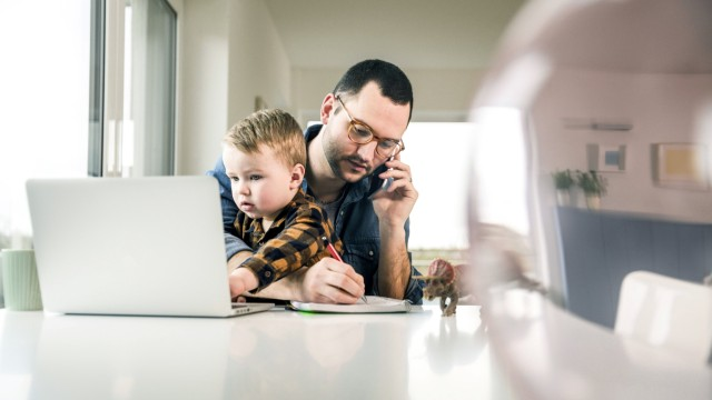 Busy father working at table in home office with son sitting on his lap model released Symbolfoto property released PUB