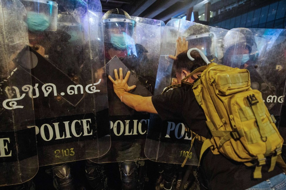 October 16, 2020, Bangkok, Thailand: A protester tries to stop riot police from dispersing the crowd during the demonstr