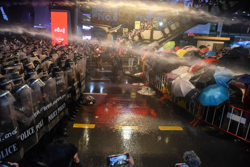 October 16, 2020, Bangkok, Thailand: Pro-democracy protesters seen covering themselves from the water cannons with umbr