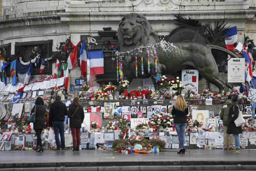 People look at flowers and messages to pay tribute to the victims of last year's January and November shooting attacks near the statue at the Place de la Republique in Paris