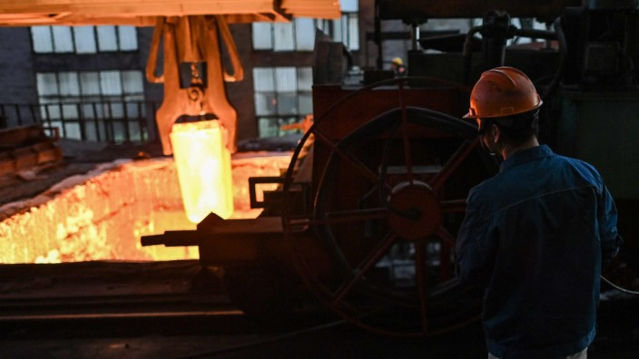 Trotz Corona-Krise: Ein Arbeiter bedient einen Kran zur Bearbeitung eines Stahlblocks in der ostchinesischen Stadt Zhenjiang.