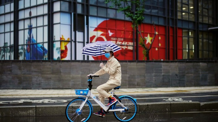 FILE PHOTO: Woman rides a shared bicycle past an image of the Chinese flag in Wuhan
