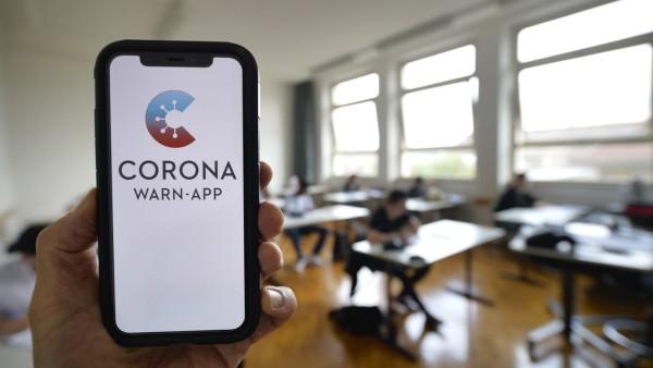 Hand hält Smartphone mit Corona Warn-APP im Klassenzimmer einer Schule, Corona-Krise, Stuttgart, Baden-Württemberg, Deu