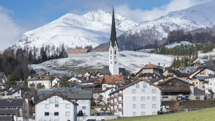 View of the alpine village of Zuoz surrounded by snowy peaks in spring Maloja Canton of Graubunden