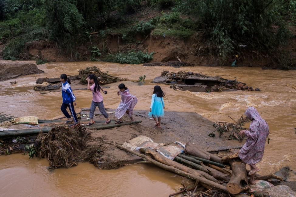 Children cross a damaged bridge following a landslide in Quang Tri province