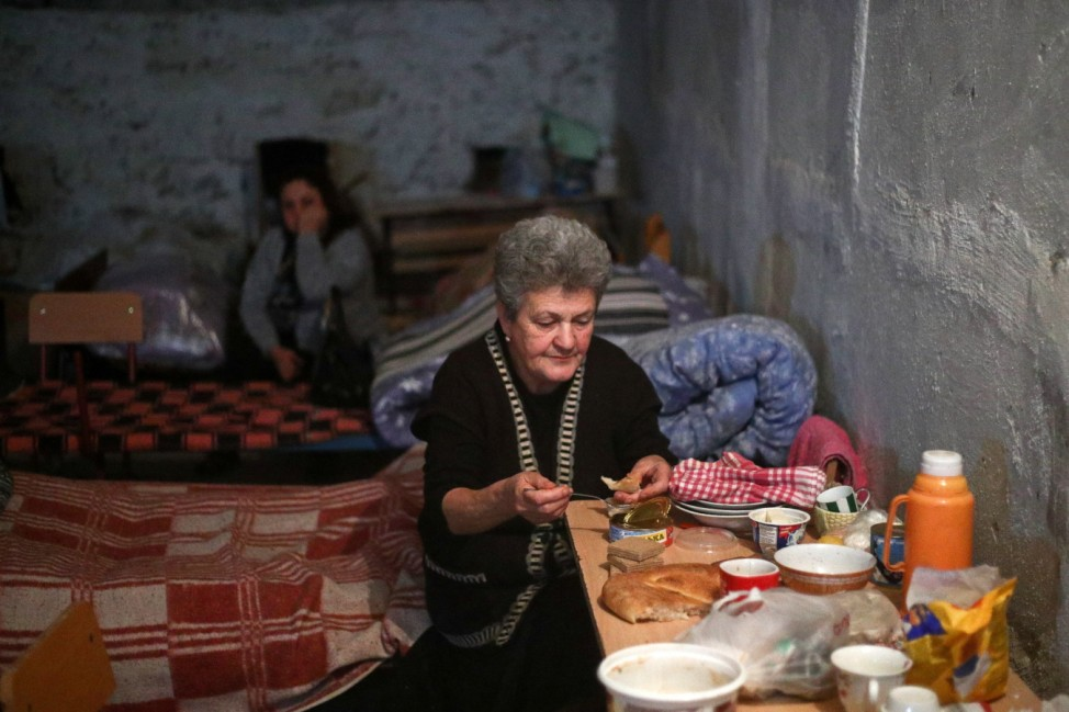 ASKERAN, NAGORNO-KARABAKH - OCTOBER 22, 2020: A woman has a meal in a bomb shelter. The fighting between Armenia and Az