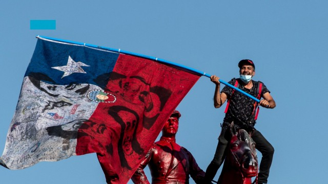 A demonstrator flutters a Chilean national flag from the top of the General Baquedano monument