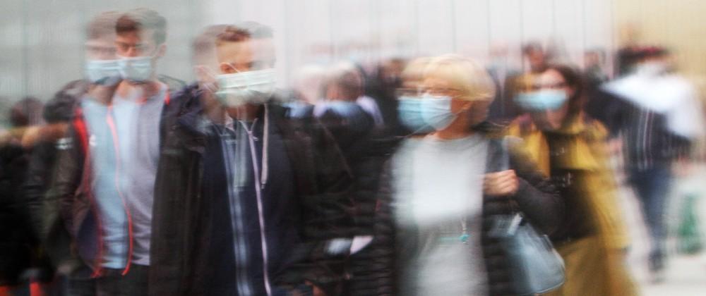 Passanten mit Mund und Nase Bedeckung spiegeln sich in einer Schaufensterscheibe in der Einkaufsstraße und Fußgängerzon