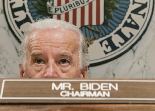 """Ein weißhaariger Joe Biden sitzt im US-Senat hinter einem Schild auf dem """"Chairman"""", Vorsitzender, steht."""