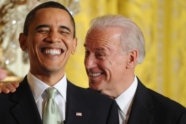 Joe Biden und Barack Obama lachen ausgelassen bei einem St. Patrick's Day-Empfang im Weißen Haus vor einer gelben Wand.