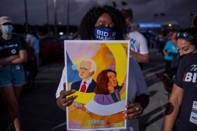 Eine Frau mit einem Mund-Nasen-Schutz der Biden-Harris-Kampagne hält ein buntes Plakat mit Illustrationen von Kamala Harris und Joe Biden in den Händen.