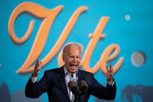 """Joe Biden spricht be ieiner Drive-In Wahlkampfveranstaltung in Florida vor einer blauen Stellwand, auf der in großen geschwungenen Lettern in gelb """"Vote"""" steht."""