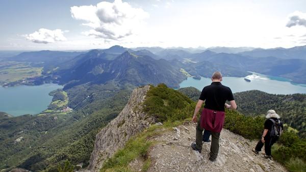 Blick vom Gipel des Herzogstands auf den Kochelsee und Walchensee, im Vordergrund fotografierende Bergwanderer