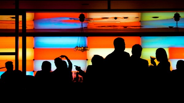 People silhouetted as they drink at a bar/club