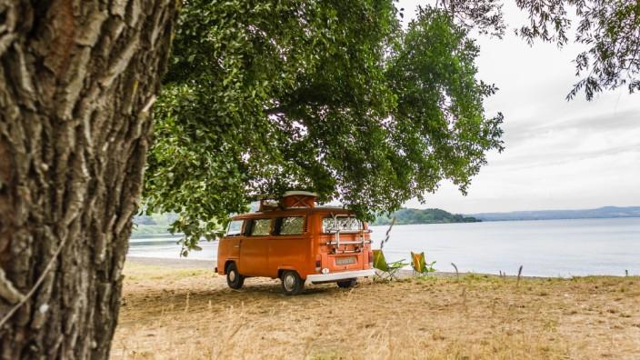 Ein Campingbus Volkswagen VW Bulli T2 steht unter Bäumen in der Landschaft an einem Seeufer, Bolsena, Latium, Italien. M; Camping