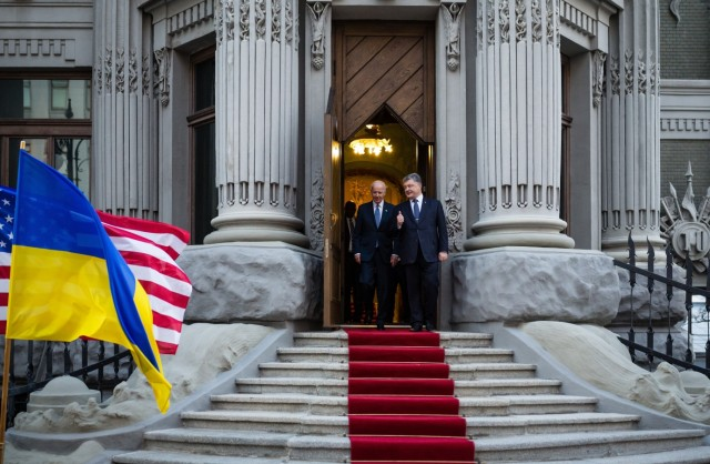 Vizepräsident Joe Biden und der ehemalige ukrainische Präsident Petro Poroshenko verlassen über einen roten Teppich ein Gebäude in Kiev im Jahr 2015.