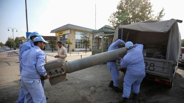 Azeri investigators load a fragment of an artillery shell following shelling in Barda