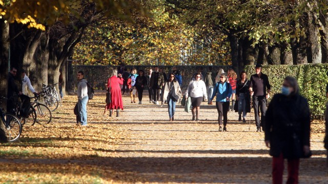 Passers-by enjoy the warm and sunny autumn day while strolling through the colorful autumn courtyard garden