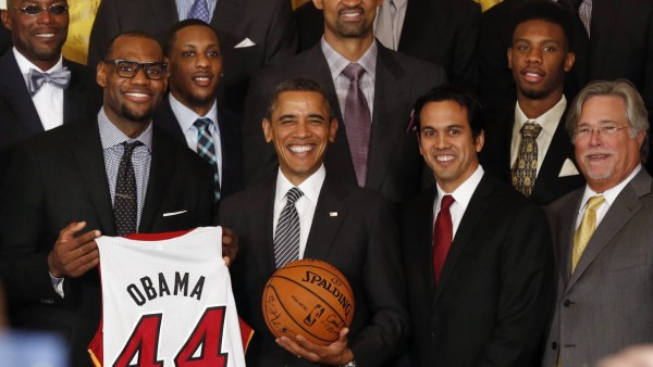Obama poses next to LeBron James as he hosts the NBA champions Miami Heat in the East Room at the White House in Washington