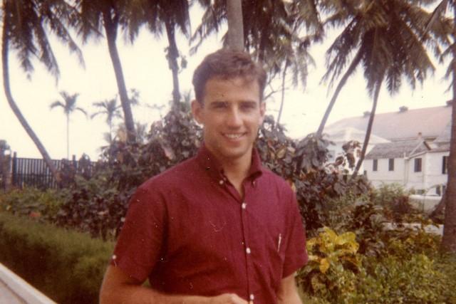 Joe Biden als Student in einem kurzärmeligen roten Hemd vor Palmen in einem Park.