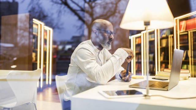 Mature man sitting at desk in a library in the evening using laptop model released Symbolfoto proper