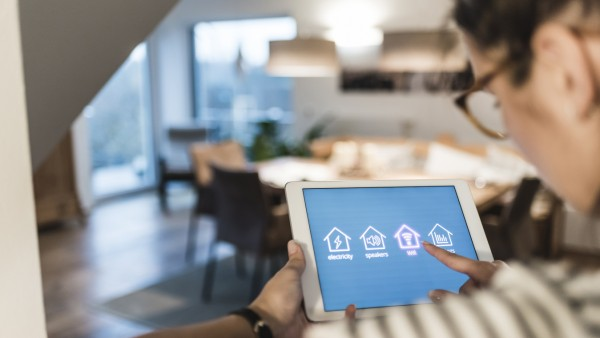 Smart Home - Woman using tablet with smart home control functions at home