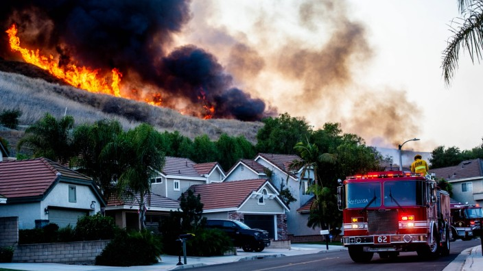October 27, 2020, Chino Hills, California, USA: Flames from the Blue Ridge Fire burns above homes along Coyote St. in C