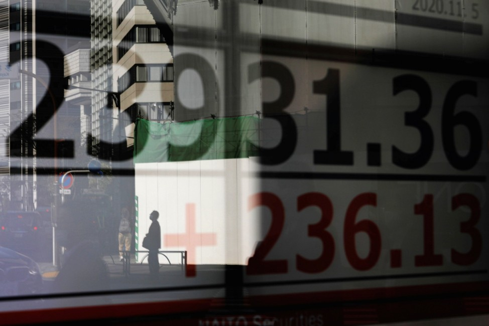 A man is reflected on a screen showing Nikkei index outside a brokerage in Tokyo