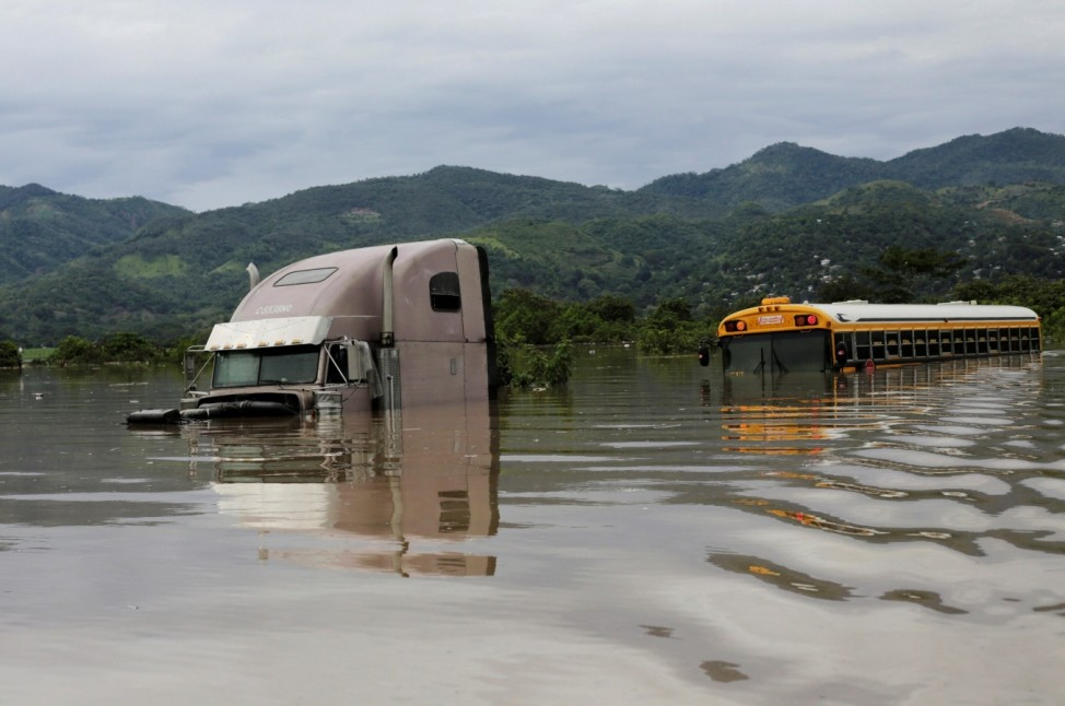 A submerged truck and a bus are seen along at a flooded street during the passage of Storm Eta, in Pimienta
