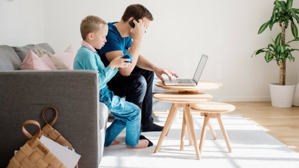 father sat at home with his son on his mobile and laptop Sweden, Stockholm County, Norrtälje PUBLICATIONxINxGERxSUIxAUTx