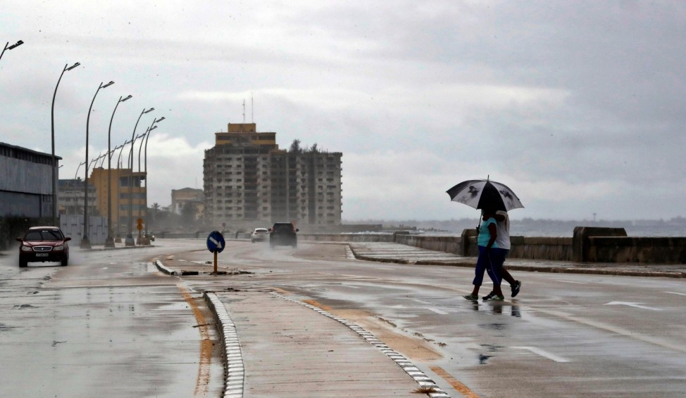 Two people protected with umbrellas from the rain cross the Malecon avenue after the Eta pass, in Havana, Cuba, 08 Nove