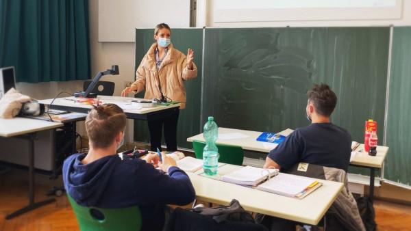 Lehrerin mit dicker Winterjacke und Mundschutzmaske im PrâÄ°senzunterricht, Gestik, Corona-Krise, Stuttgart, Baden-W¸rtte