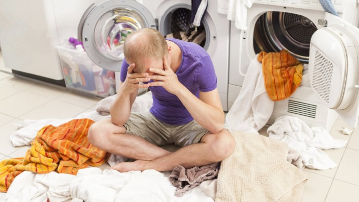 Young man sitting between dirty laundry model released Symbolfoto PUBLICATIONxINxGERxSUIxAUTxHUNxONL