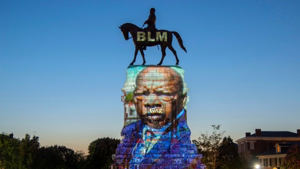 The image of late Rep. John Lewis, a pioneer of the civil rights movement and long-time member of the U.S. House of Representatives, is projected on the statue of Confederate General Robert E. Lee in Richmond