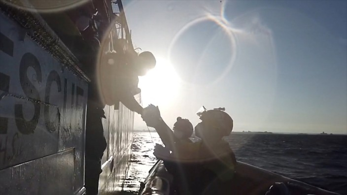 A still image taken from a video shows a rescuer of Spanish NGO Open Arms helping a migrant boarding a dinghy in the Mediterranean Sea