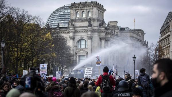 Polizisten agieren mit Wasserwerfern gegen Demonstranten, die gegen die Reform des Infektionsschutzgesetzes protestiere