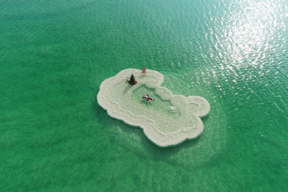 An aerial view shows Issa Kassissieh, wearing a Santa Claus costume, and floating next to a Christmas tree on a salt formation in the Dead Sea, near Ein Bokeq