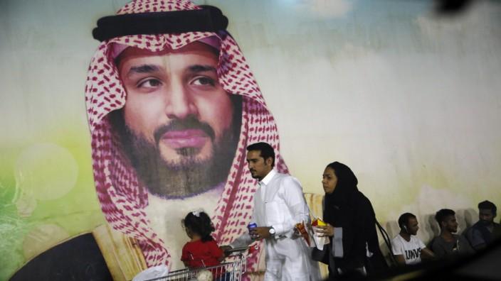 A Saudi family walk past a giant poster of Saudi Crown Prince Mohammed bin Salman