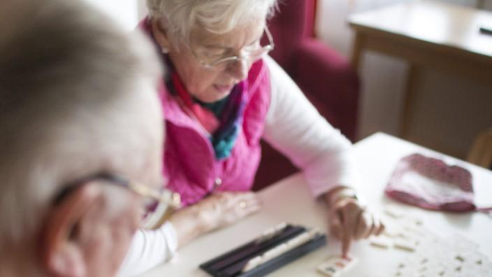 90 jaehriger Bewohner des Alten und Pflegeheims spielt mit 75 jaehriger Frau ein Gesellschaftsspiel