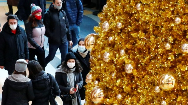 People wear protective face masks as they walk beside Christmas decoration amid the coronavirus disease (COVID-19) outbreak in Berlin
