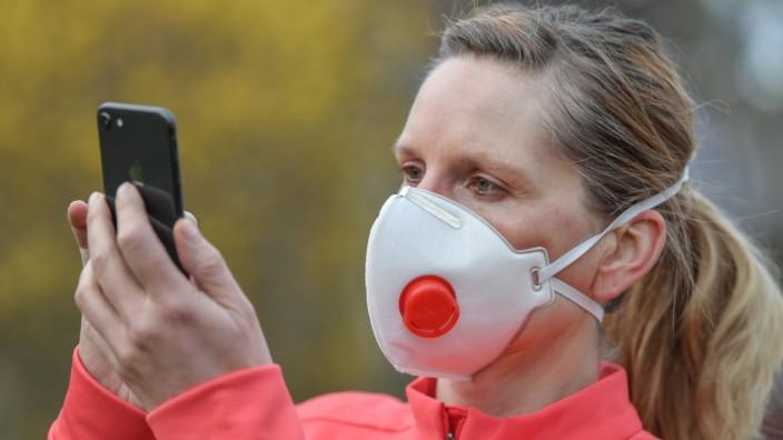 Coronavirus - Frau mit Atemschutzmaske und Handy