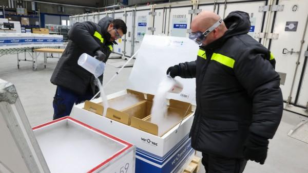 """Corona-Impfstoff: Mitarbeiter der Firma """"Va-Q-Tec"""" füllen Trockeneis in Transportboxen"""