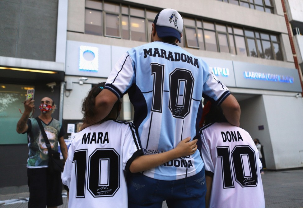 Fans of Argentine soccer great Diego Maradona pose for a photograph outside the clinic where Maradona underwent brain surgery, in Olivos